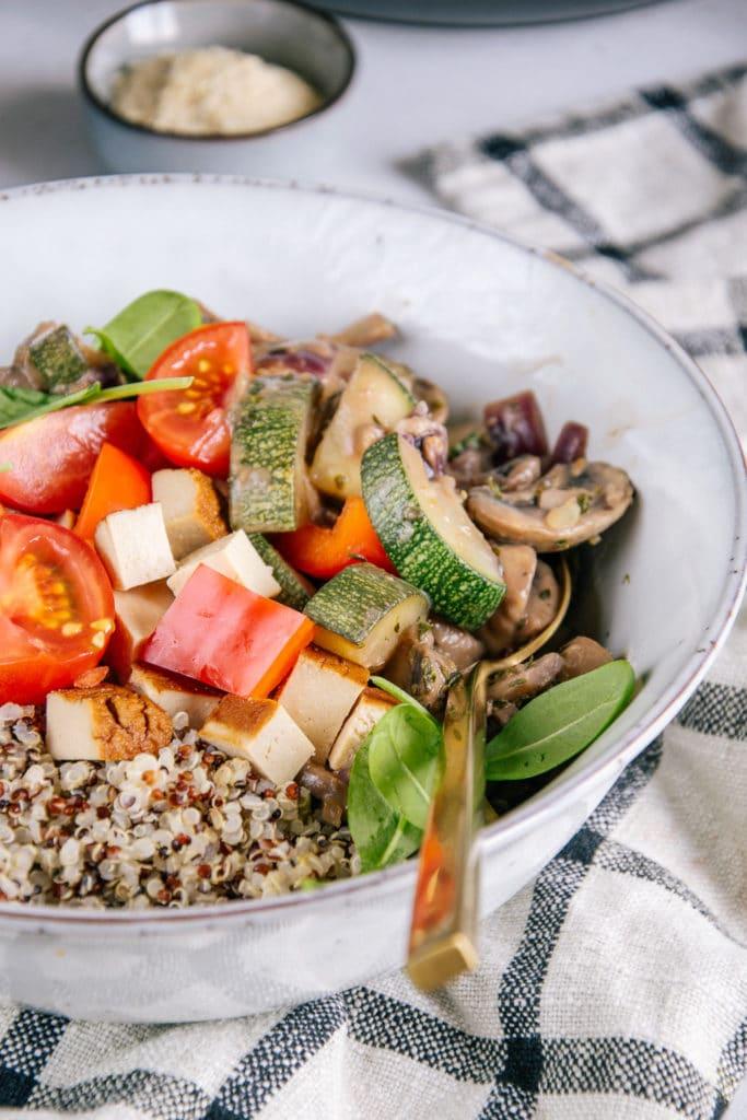 Quinoa, Räuchertofu, Tomaten und cremige Pilzpfanne in einer graublauen Schüssel. Nahaufnahme im 45-Grad-Winkel