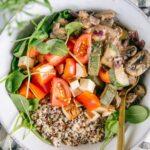 Nahaufnahme von cremiger veganer Pilzpfanne mit Quinoa, Räuchertofu, Tomaten und Jungspinat in einer graublauen Bowl mit goldenem Löffel.