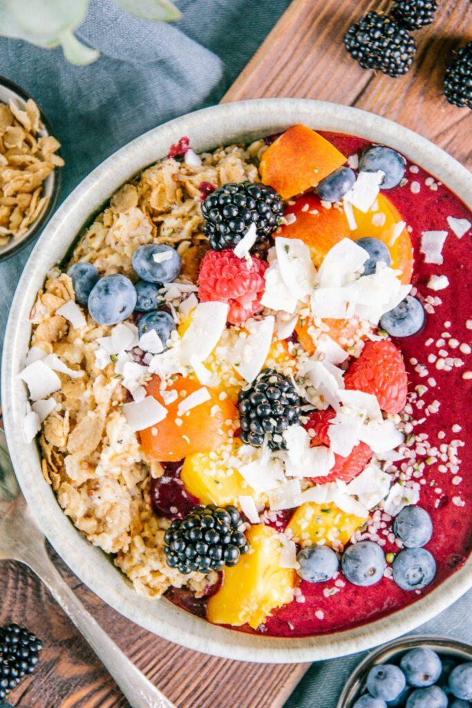 Nahaufnahme in Vogelperspektive von Porridge mit Nicecream. Topping aus Nektarinenstücken, gemischten Beeren, Kokoschips und Hanfsamen.