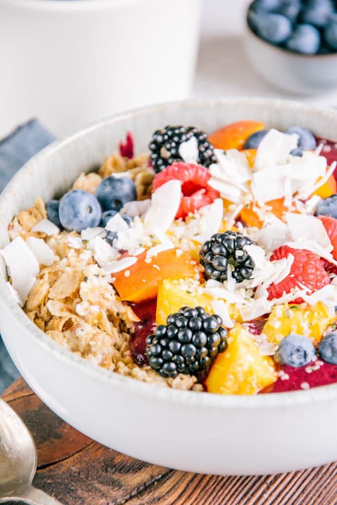 Porridge mit Nicecream im 45-Grad-Winkel aus der Nähe fotografiert, sodass die Details von Haferflocken und buntem Früchte-Topping deutlich erkennbar sind