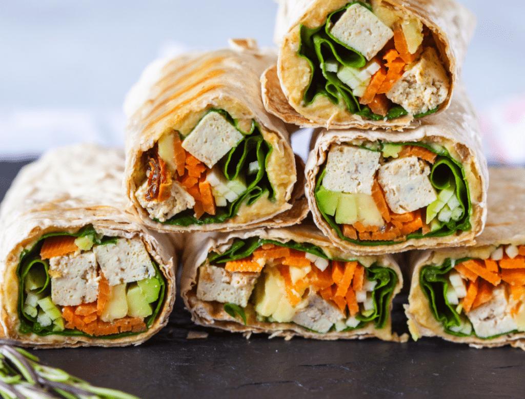 Vegan gefüllte Wraps auf Augenhöhe aufgenommen. Erfrischend aussehende Füllung mit Tofu, Avocado, Spinat, Hummus und Karotten.
