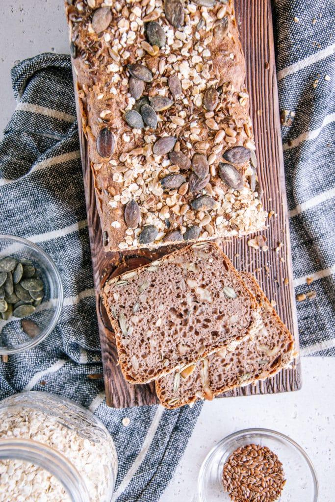 Angeschnittenes Vollkorn-Walnussbrot auf einem Holzbrett. Das Brot ragt von oben ins Bild und zwei Scheiben liegen bereits abgeschnitten daneben.