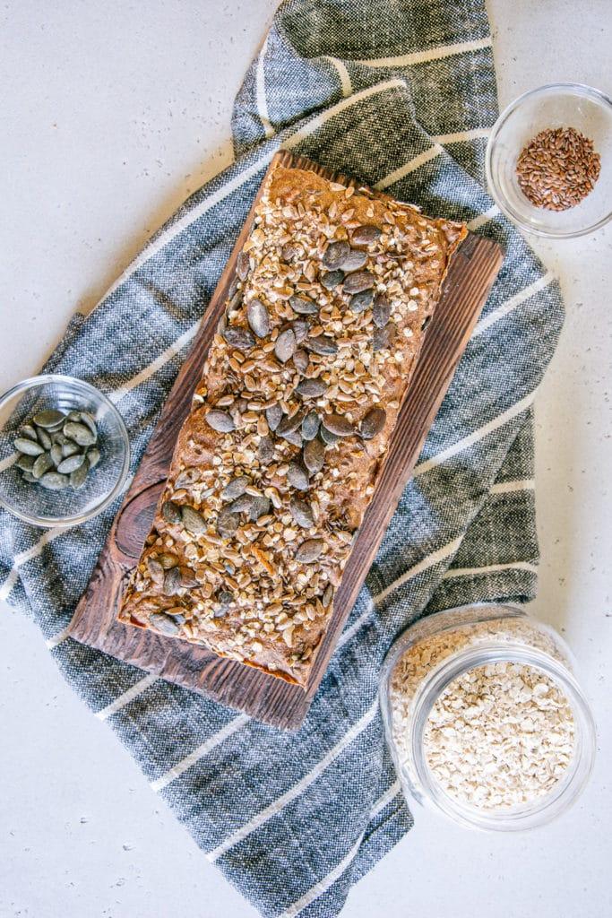 Vollkorn-Walnussbrot aus der Vogelperspektive diagonal im Bild ausgerichtet. Das Brot liegt auf einem Holzbrett, das auf einem gestreiften Küchentuch steht.