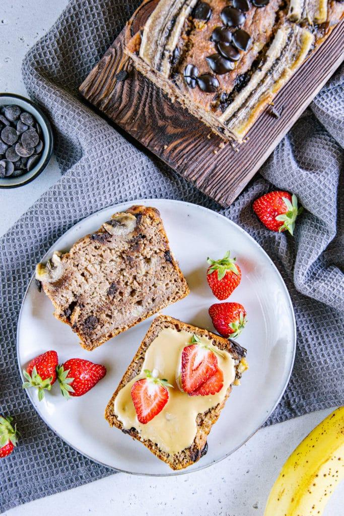 Zwei Scheiben gesundes veganes Chocolate Chip Bananenbrot auf einem graublauen Teller. Eine davon ist mit Mandelmus bestrichen und mit Erdbeeren belegt. Aufnahme von oben.