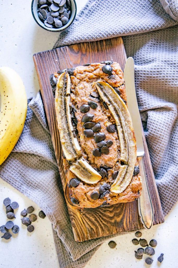 Gesundes veganes Chocolate Chip Bananenbrot auf einem rustikalen Holzbrett und einem grauen Küchentuch. Aufnahme aus der Vogelperspektive.