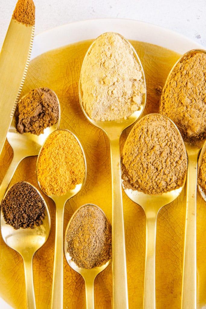 Alle Gewürze für Pumpkin Spice auf goldenen Löffeln aufgelegt auf einem ockerfarbenen Teller. Nahaufnahme von oben.