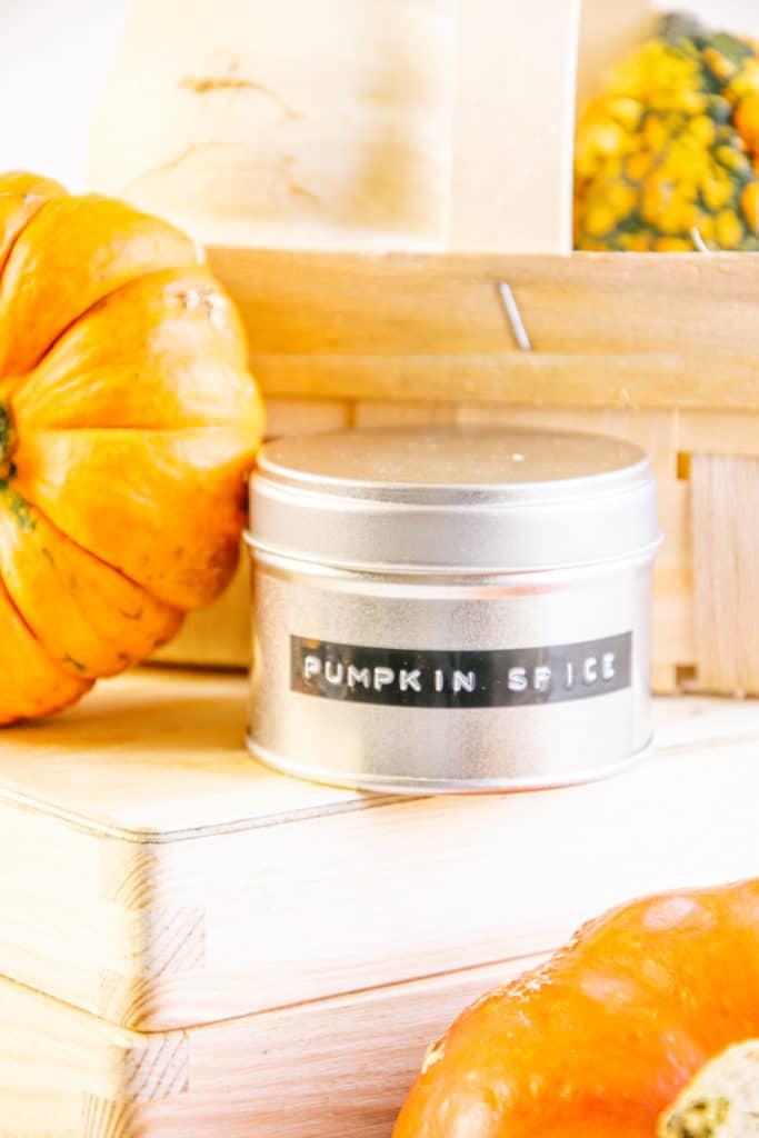 """Gewürzdose mit der Aufschrift """"Pumpkin Spice"""" auf einer Holzbox neben einem Zierkürbis. Aufnahme aus der Fronalansicht."""