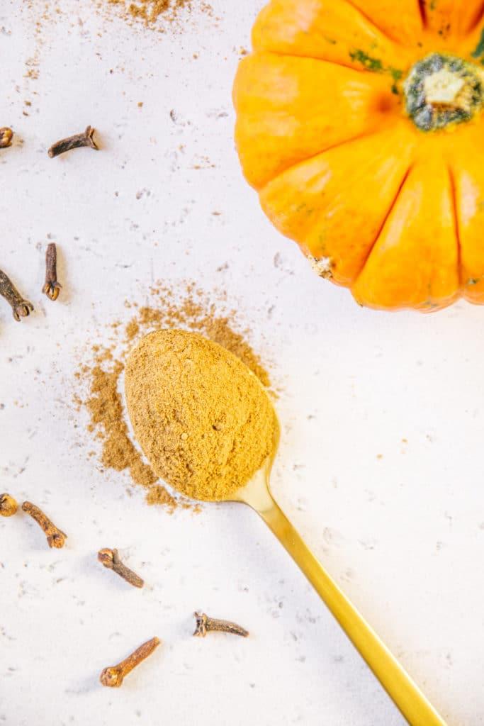 Goldener Löffel mit Pumpkin Spice auf weißem Untergrund mit Gewürznelken und Zierkürbis