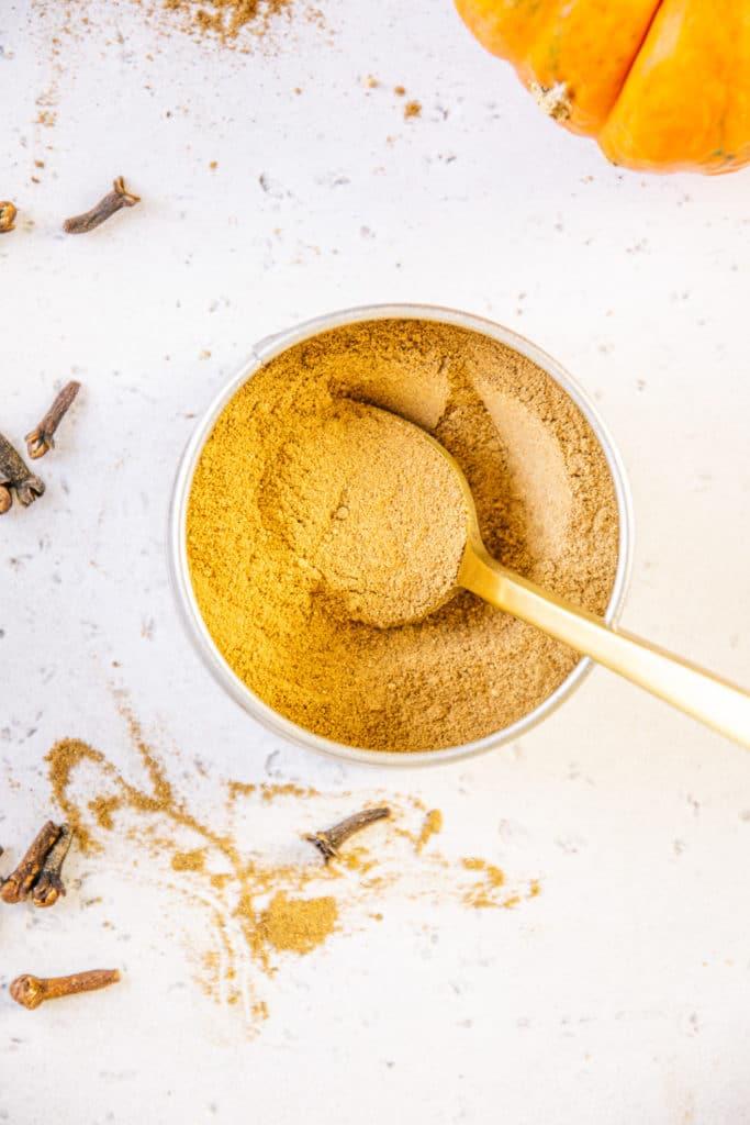 Offene Gewürzdose mit Pumpkin Spice und einem goldenen Löffel darin