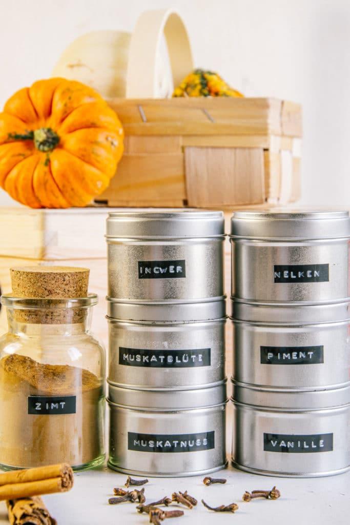 Gewürze für Pumpkin Spice in Gewürzdosen gestapelt und Glas mit Zimt daneben. Aufnahme aus der Frontalansicht.